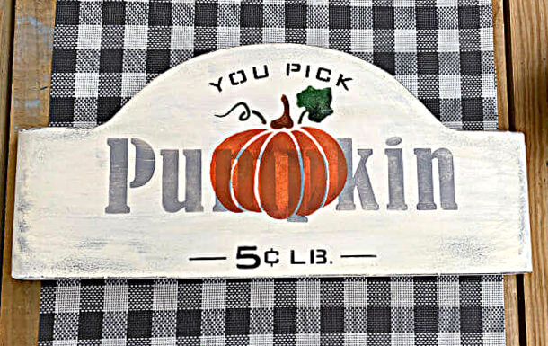 stenciled pumpkin sign with a buffalo check background