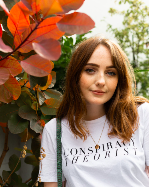 "girl standing near autumnal leaves, wearing ""conspiracy theory"" t-shirt"