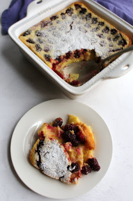 serving of blackberry clafoutis on plate in front of pan of remaining clafoutis