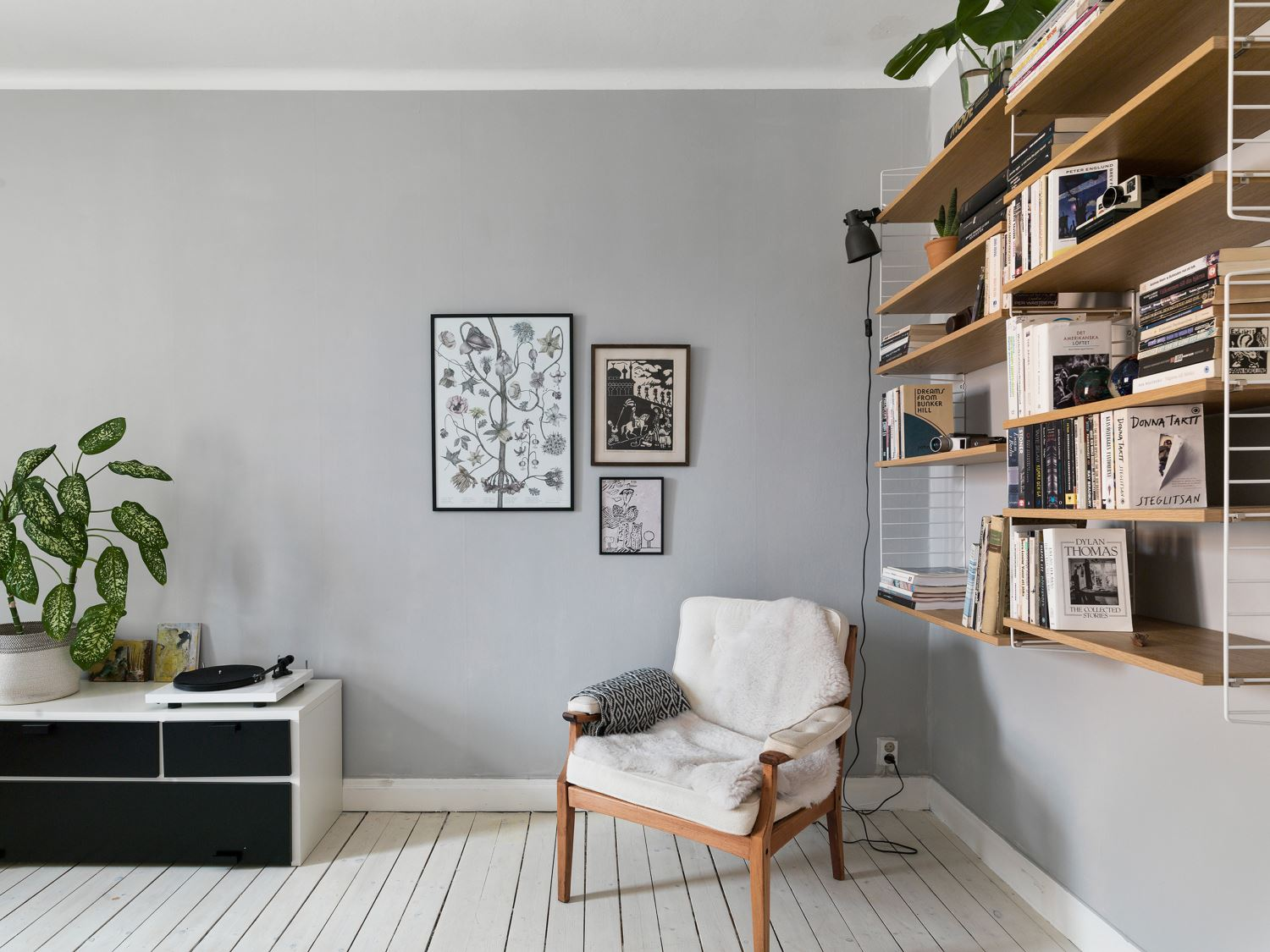 serene scandinavian duplex apartment with botanical print, white floor and string shelf