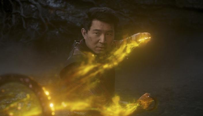 Imagem: o personagem Shang-Chi, em posição de luta, com uma camisa de cordões vermelha com aplicações de metal, puxando os anéis com uma força de energia amarela fluindo por entre eles e um fundo cavernoso.