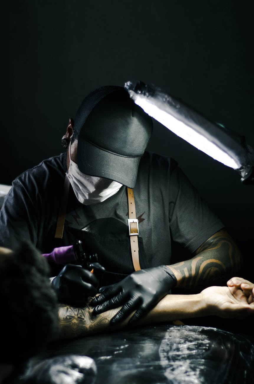 Photo of a male tattoo artist working on a tattoo - Man is holding the tattoo gun and it is touching a customers skin. He is wearing a white mask with a black baseball cap on, grey t-shirt and black gloves.