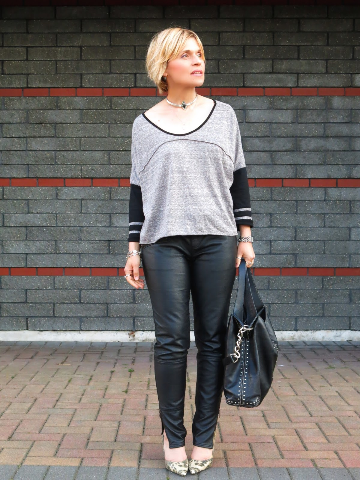 styling vegan leather jeans with long-sleeve baseball tee and animal-print pumps