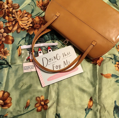 An ochre handbag lying on an apple green and ochre scarf