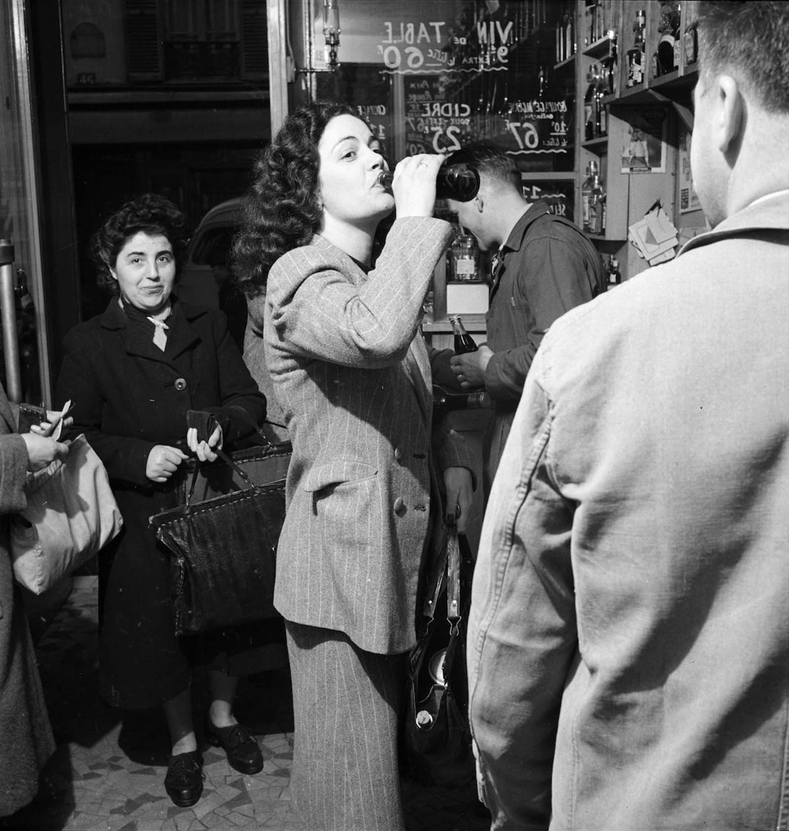 A young woman drinks a bottle of Coca-Cola in a Paris shop.