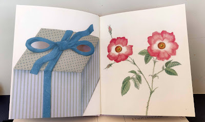 The following spread in the book Ojos that reveals a present on the left hand side and two flowers on the right hand side. The center of the two flowers made up the pupils of the original eye image.