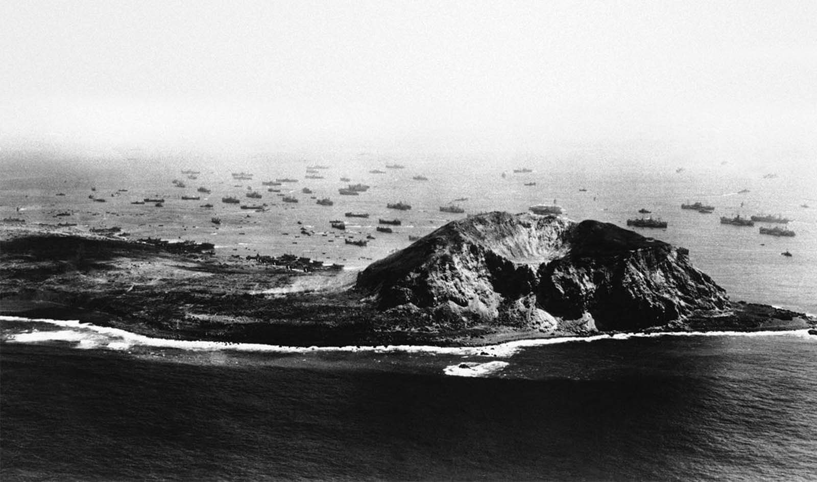 This aerial photograph made on day five of the invasion shows the immense power needed to break the back of Japanese Resistance on Iwo Jima, on March 17, 1945. Just off the beach, landing craft await their chance at the unloading area while small boats from the transports ply back and forth bring assault troops and returning wounded for treatment. Further out, the transports themselves faintly along the horizon, the protective screen of destroyers, destroyer escorts and cruisers can be seen. On the island, Marine tanks can be spotted moving through the rough terrain toward the first airfield at left.