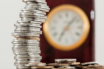 Stos monet, w tle rozmyty zegar naścienny