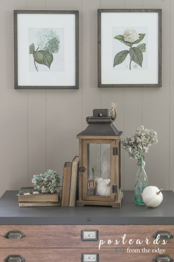 vintage hydrangea printable art with glass lantern, old books, and dried hydrangeas