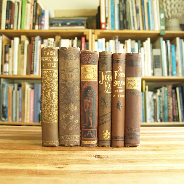 Six antique books in brown and red decorative bindings
