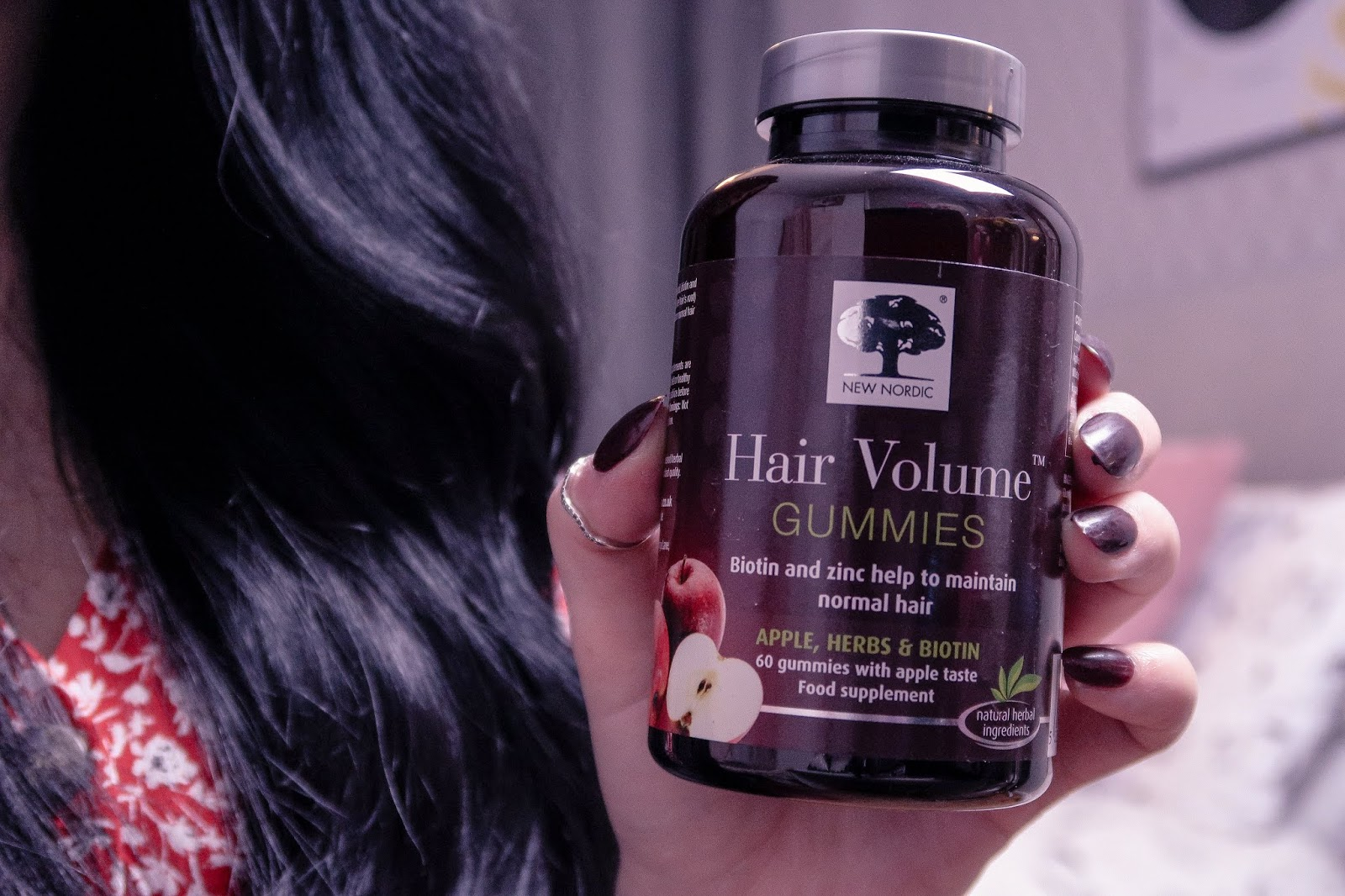 Close up photo of girl holding New Nordic Hair Volume gummy Supplements - Wearing a red dress with white flowers, long black curled hair over left shoulder, New Nordic Supplements bottle is dark purple with white writing.