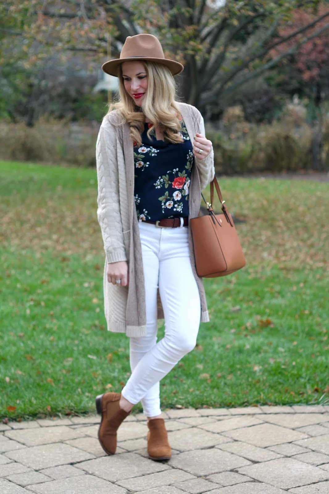 aventura cardigan, camel cable knit cardigan, navy floral blouse, white jeans, cognac booties, Tory Burch tote, camel fedora
