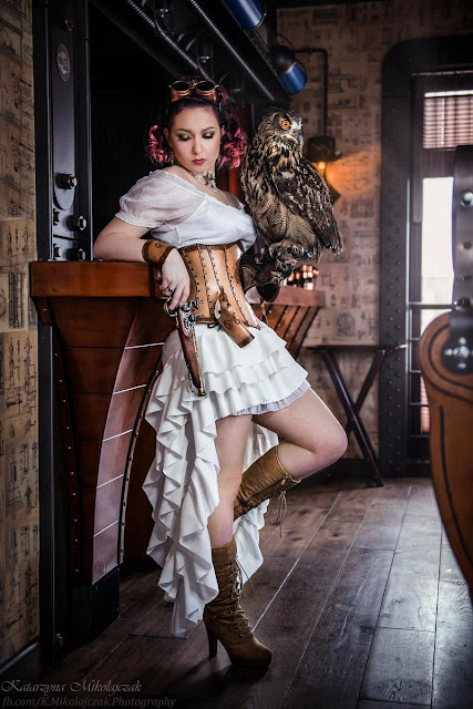 woman wearing steampunk clothing, holding a live owl. goggles, leather corset, skirt, blouse, boots.