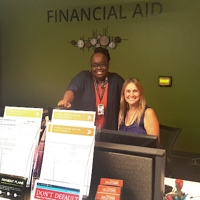 Photo of financial aid office with smiling staffers behind the service counter.