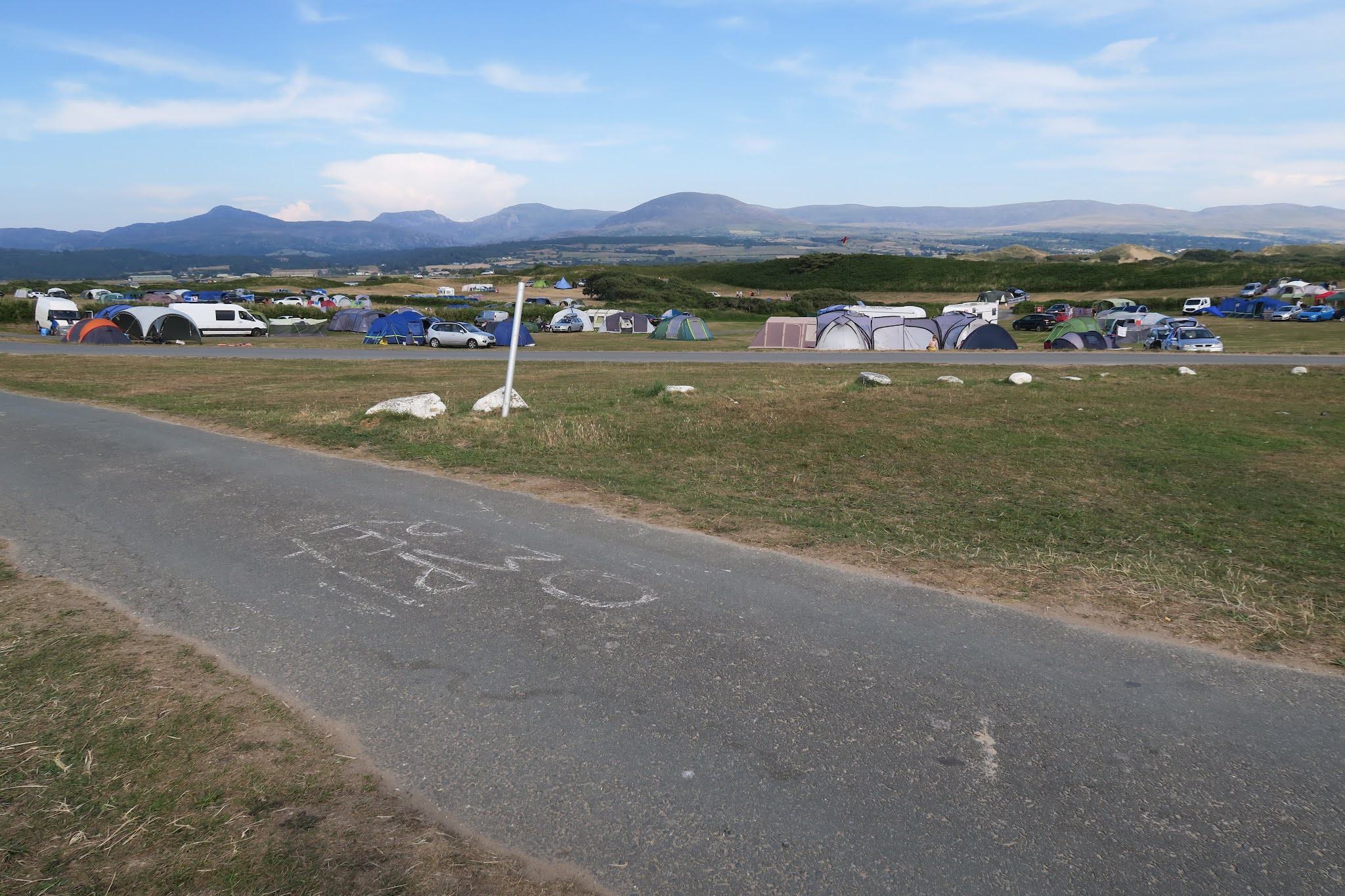 Looking across the campsite. Tents and campervans are scattered across the land. The mountainous Snowdonia National Park can be seen in the background.