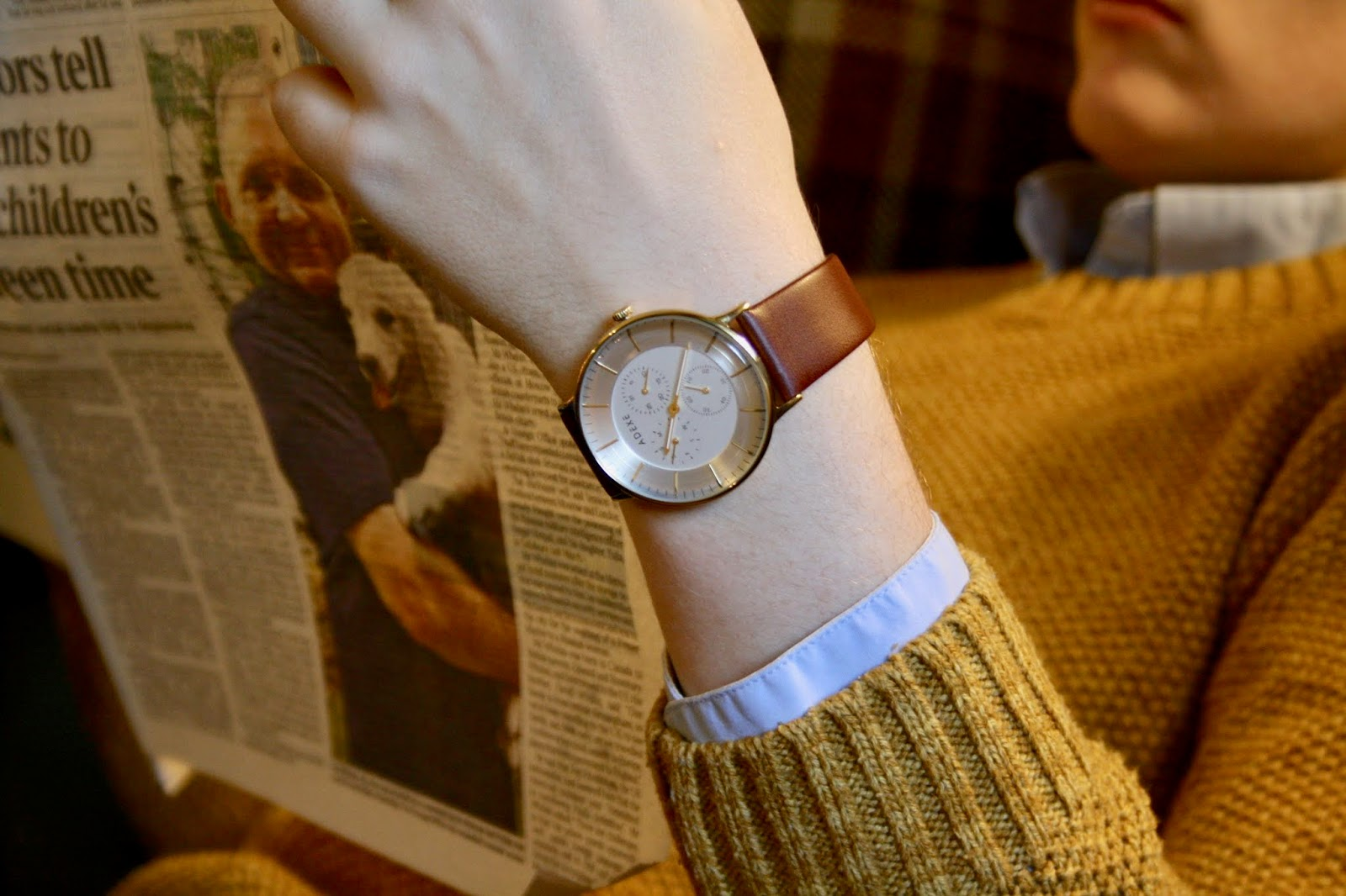 close up of a gold watch face, blue shirt cuff and mustard jumper, a newspaper in the background