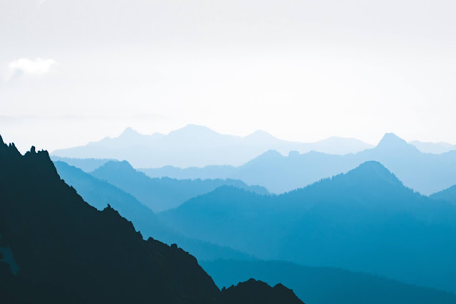 A mountain range silhouetted in blue against a white sky