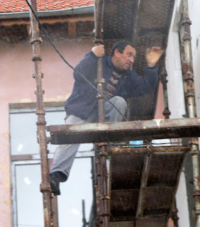 Bekir up a scaffold in the rain