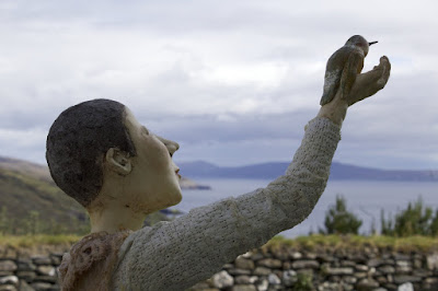 Sculpture by Corina Duyn, showing a head and outstreched arm with a bird in the hand. view of sea and cliffs.