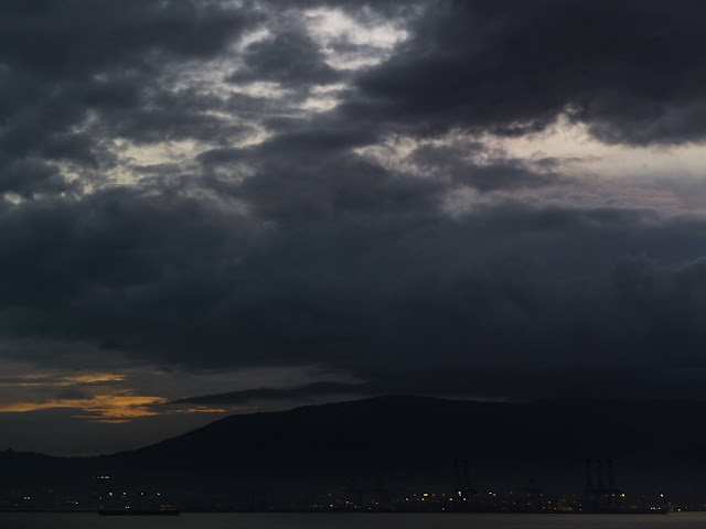 Dark clouds in the port of Gibraltar after sunset with lights in the foreground..