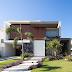 Fachada de casa contemporânea com volumetria, painel ripado de madeira e pedras vulcânicas!