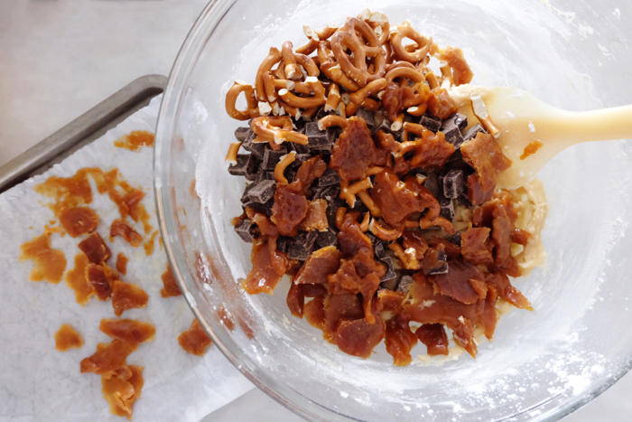 mixing in chips, pretzels, and caramel bits