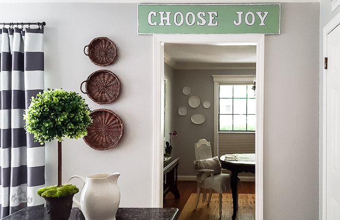 baskets on wall, green sign, artificial boxwood topiary and striped curtains