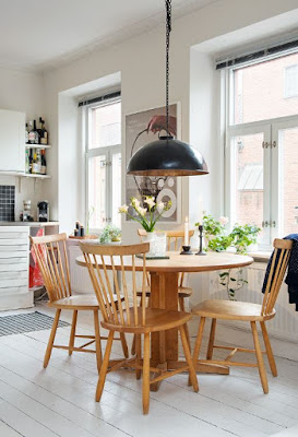 Nice Scandinavian dining room with round wooden dining table with indoor plants decor