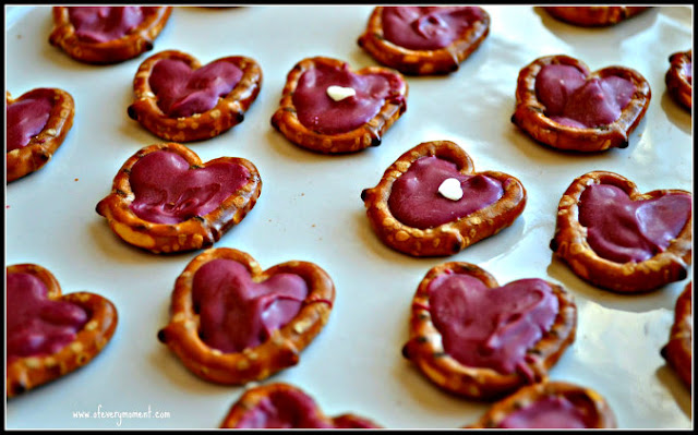 A tray of heart shaped pretzel candies with red fillings.