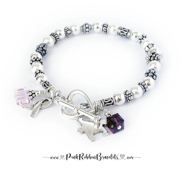 This Pink Ribbon Bracelet is shown with a Pink and Purple Swarovski crystal charm,Ribbon Charm , Puzzle Piece Charm and they upgraded to a Heart Toggle Clasp.