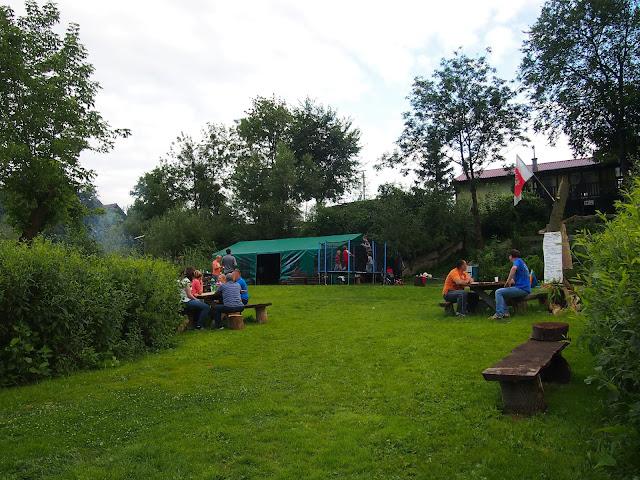 Pole namiotowe skąpane w zieleni. Goście odpoczywają siedząc na ławach. W tle namiot biesiadny.