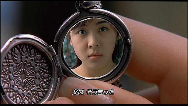 ハ・ジウオンの顔がペンダントの中の鏡に映っている