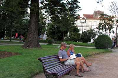 Casal sentdo num banco de jardim lendo livros