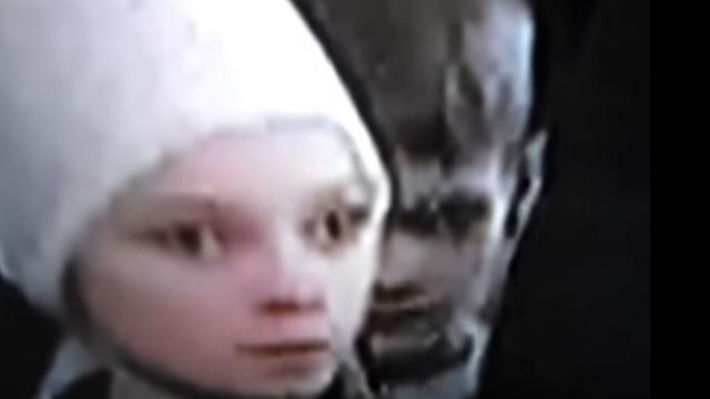 Deathly grey Demin child behind Putin.