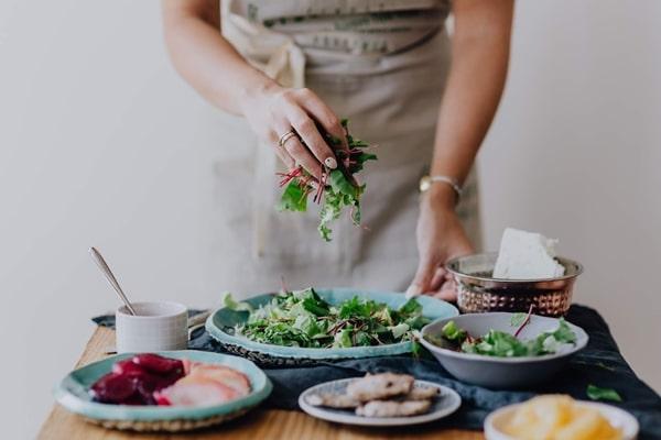 Mulher do ombro para baixo cozinhando salada