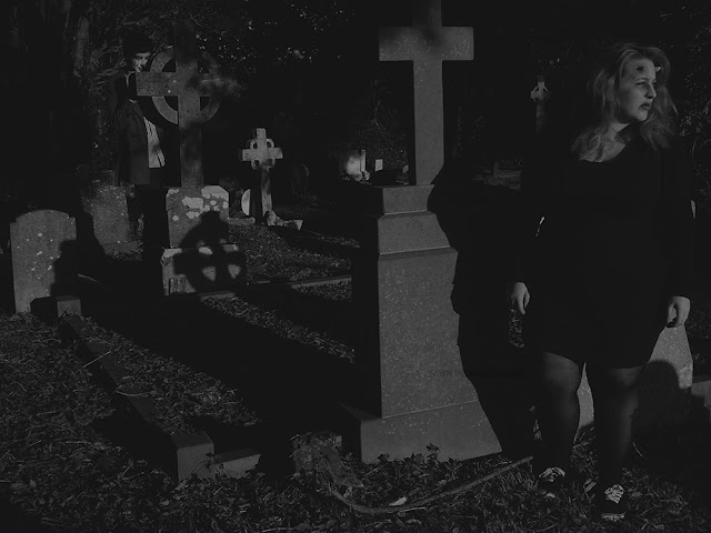 Horned woman being stalked by a creepy man in a cemetery