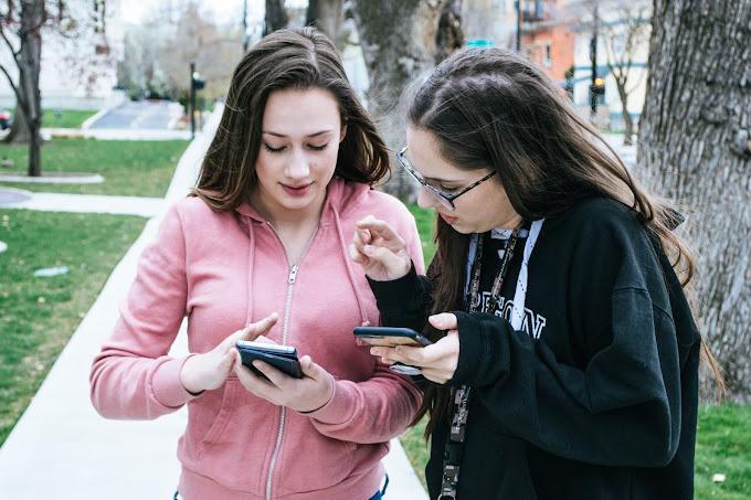 Duas mulheres jovens usando seus celulares na praça. Elas estão em pé, próximas e usam moletom.