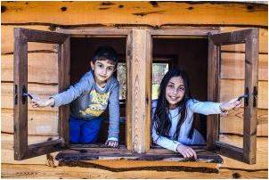 A boy and a girl each opening their window, smiling