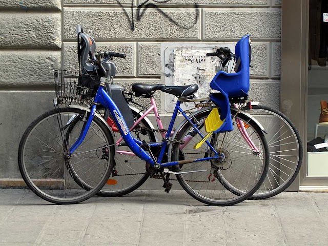 Two bicycles locked in almost perfect symmetry, via Ricasoli, Livorno