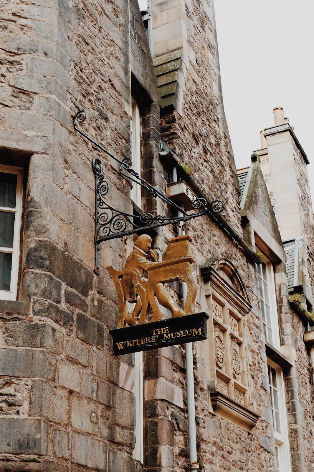 The brass sign outside the Writer's Museum on the Royal Mile of a writer at a desk
