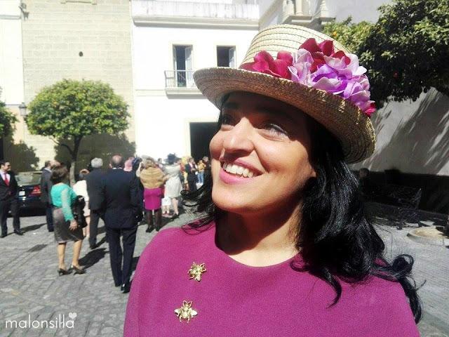 Invitada a boda de invierno con sombrero copa alta tipo chistera de flores en color buganvilla y burdeos, broches de insectos dorados