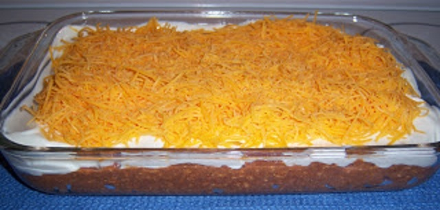 the is a Mexican refried bean dip in a large 13 x 9 glass casserole dish.