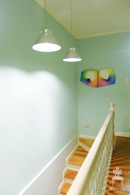 light blue hallway with light wood stairs and flooring