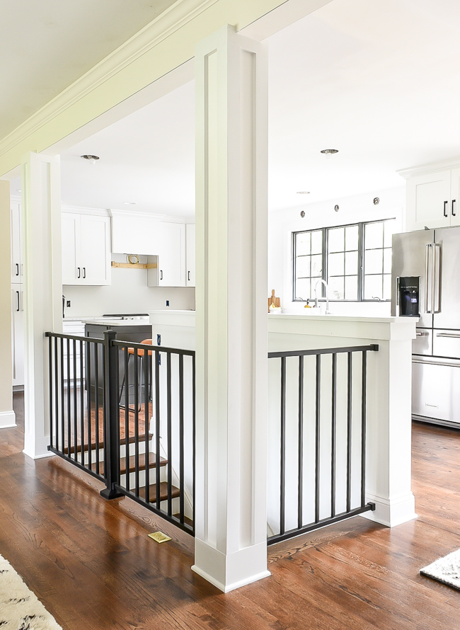 Open stairs in a rancher style home. craftsman columns with black modern railing