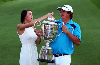 Amanda lifting the trophy with her husband Jason