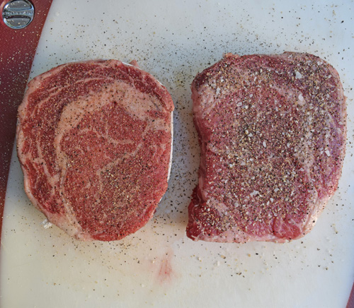 A pair of certified angus beef® Brand ribeye steaks, seasoned and ready for the grill.