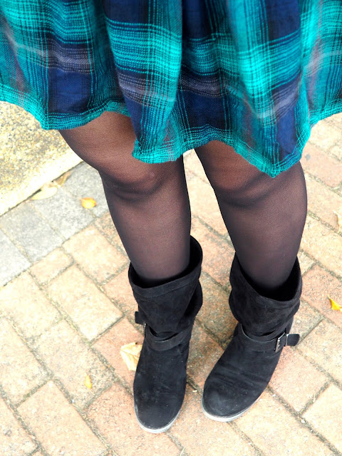 Hooded - outfit close up details of green tartan print dress hem, dark tights, and chunky, slouch, black suede boots
