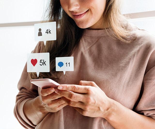 mulher usando o celular com simbolos de marketing e redes sociais