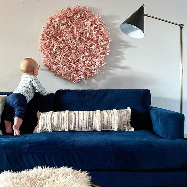 large-scale circular quilled wall hanging hangs over couch