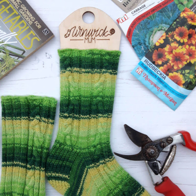 A close up of the cables on a green and yellow striped sock.  Around the socks on a board background are a book, some secateurs and some seed packets